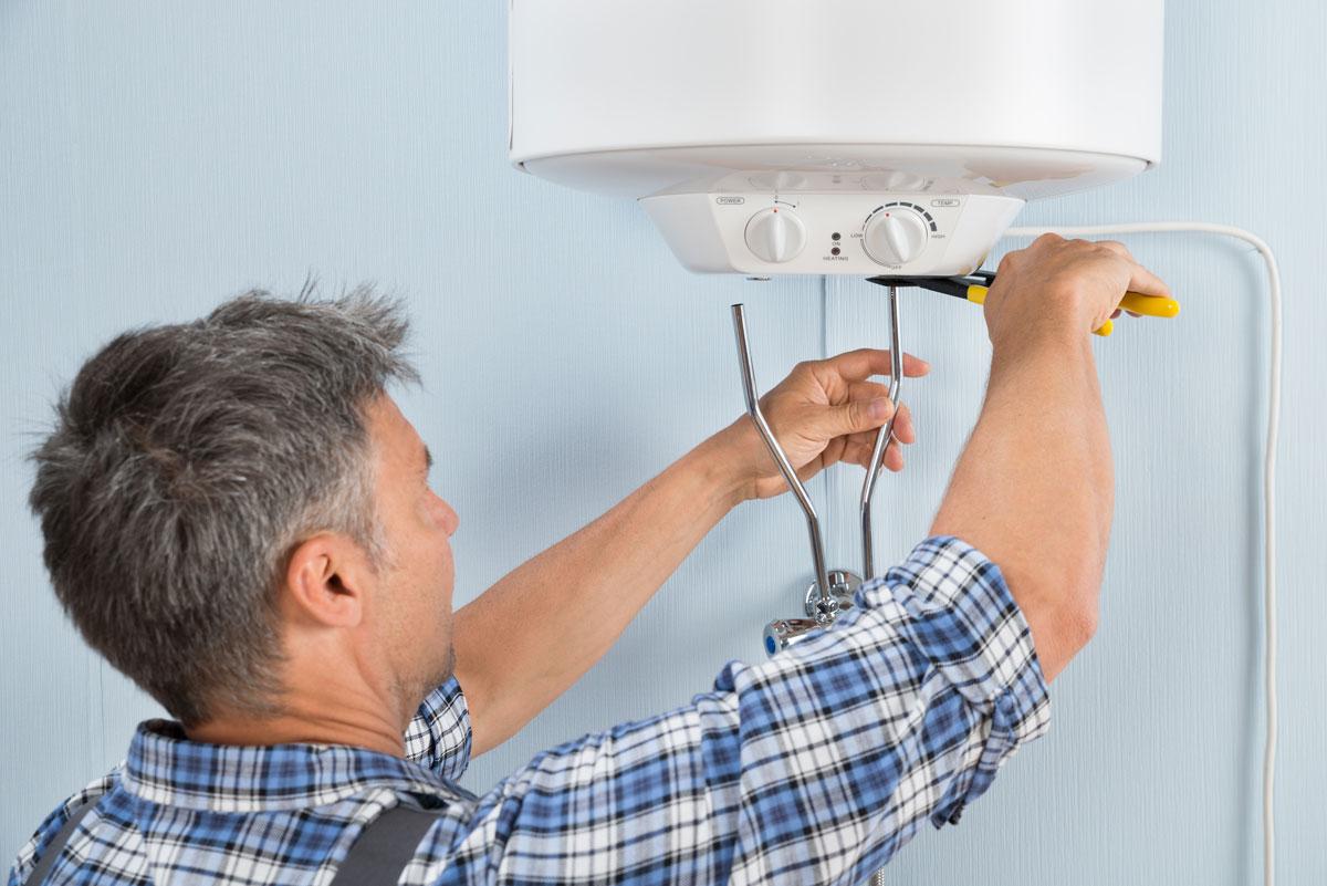 Мужчина ремонтирует водонагреватель