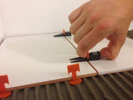 Клинья для укладки плитки (19 фото): клинышки для выравнивания керамического покрытия, набор пластиковых зажимов